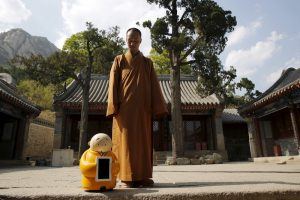 Master Xianfan looks at robot monk Xian'er as he prepares to pose for photograph in the main building of Longquan Buddhist temple on the outskirts of Beijing, April 20, 2016.  REUTERS/Kim Kyung-Hoon   - RTX2B4DN